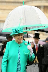 Britain's Queen Elizabeth II shelters from the rain under a fulton umbrella